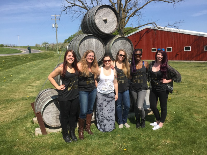 A diverse group of women in front of wine barrels.
