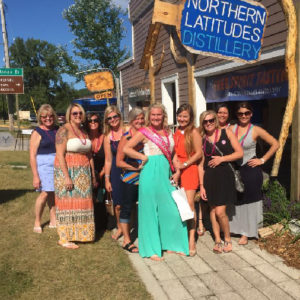 Group of women celebrating a bachelorette party wearing matching necklaces standing in front of a distillery
